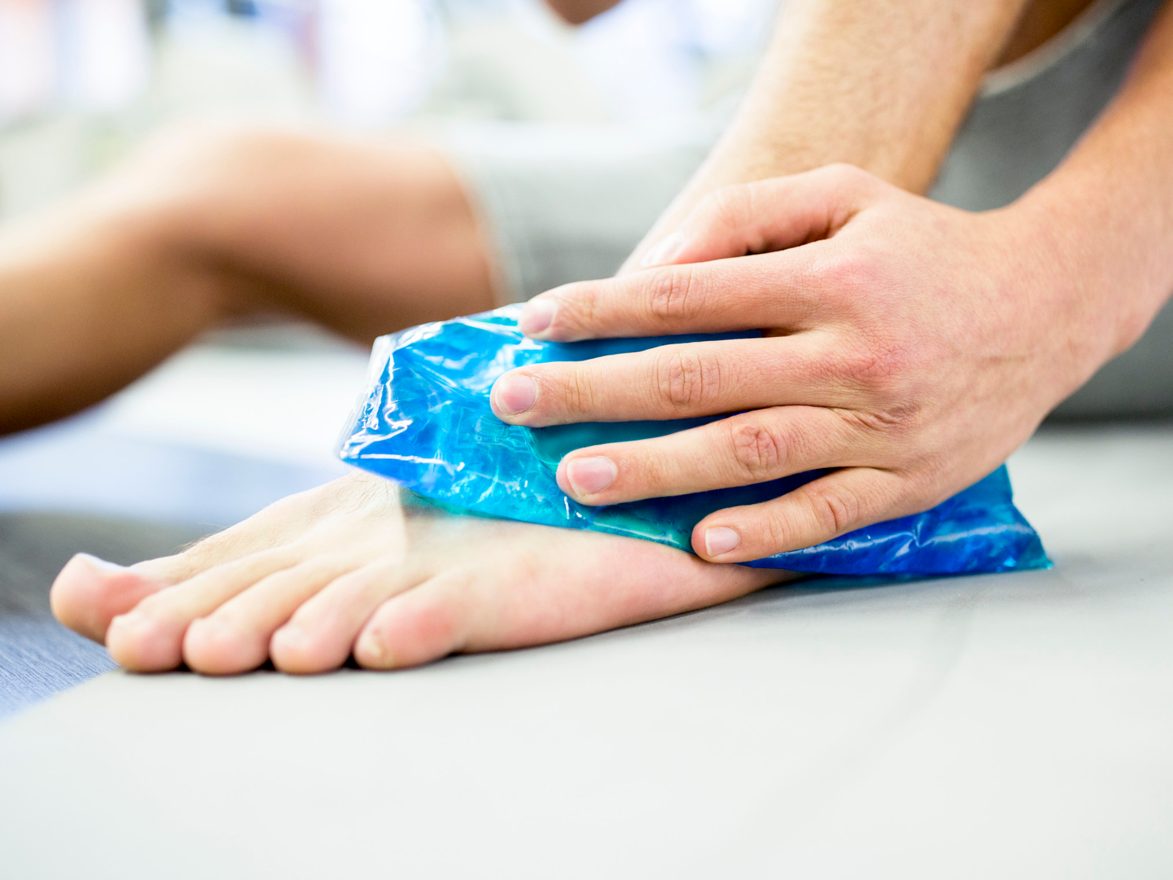 Person holding ice pack on ankle injury